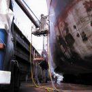 Обмыв водой под высоким давлением корпуса судна в доке